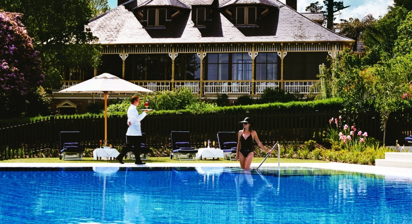 Photo of women entering hotel pool. Waiter in background.